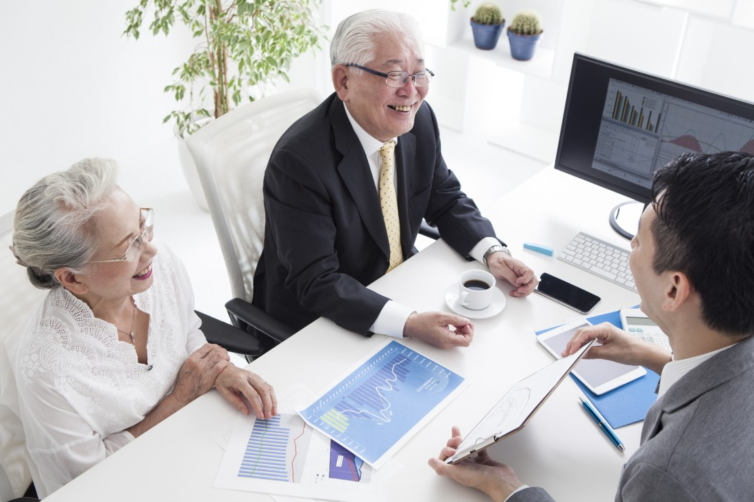 Sales person and old couple are simulating real estate investment